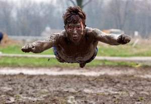 A student jumping into mud on Muddy Sunday