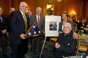 Congressmen Mike Kelly and Steny Hoyer, and House Democrat Leader Nancy Pelosi present Father Hesburgh with an American flag