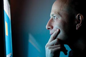 A man looking at a computer monitor