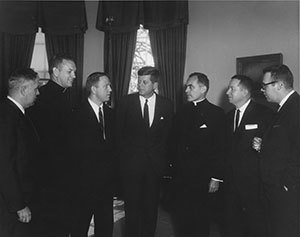 President John F. Kennedy is presented the 1961 Laetare Medal in the Oval Office. Attending the presentation (L-R): unidentified man; Father Edmund P. Joyce, C.S.C., vice president of Notre Dame; Rep. John Brademas, Indiana; Kennedy; Rev. Theodore M. Hesburgh, C.S.C., president of Notre Dame; James E. Murphy, director of public relations at Notre Dame; and an unidentified man.