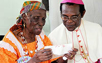 Cardinal Felix, right, talks to an elderly woman