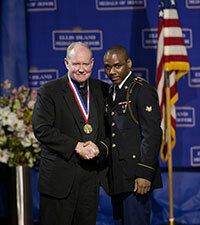 Rev. Timothy Scully, C.S.C., is pictured with a member of the Joint Service Color Guard, who presented him with his Ellis Island Medal of Honor. Photo courtesy of the National Ethnic Coalition of Organizations.