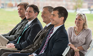 John Affleck-Graves, middle, sits with Mayor Pete Buttigieg, second from right, at the ND Turbomachinery Facility groundbreaking ceremony