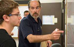Daniel Karmgard, research assistant professor of physics, instructs a student at the Notre Dame QuarkNet Center