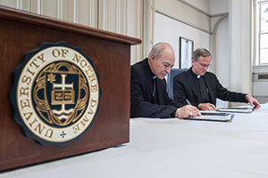 Rev. John Jenkins, C.S.C., and Archbishop Carlos Aguiar Retes, archbishop of Tlalnepantla, Mexico, and president of the Latin American Bishops' Conference (CELAM), sign a Memorandum of Understanding
