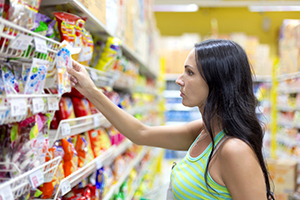 a woman looks at an item on a supermarket shelf