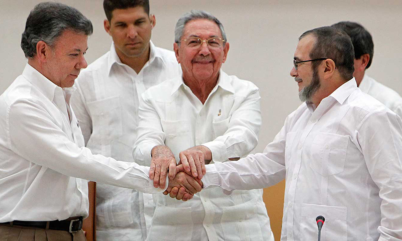 Havana, Cuba. September 23, 2015, President Juan Manuel Santos of Colombia (left in the photo) and the head of the FARC, Comandante Timoschenko (right in the photo) shake hands during a ceremony announcing the first agreement for peace. Never before had a Colombian President and a FARC comandante shaken hands.