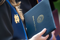 A new graduate holds her diploma following Commencement