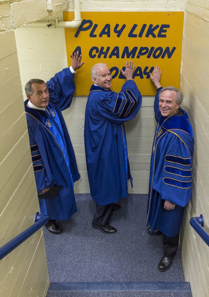 President Rev. John Jenkins, C.S.C., and Laetare Medal recipients John Boehner and Vice President Joe Biden touch the Play Like a Champion sign on their way out of the locker room for the 2016 Commencement Ceremony