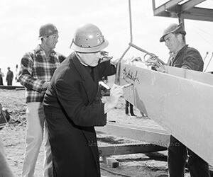 Fr. Hesburgh signs memorial library beam