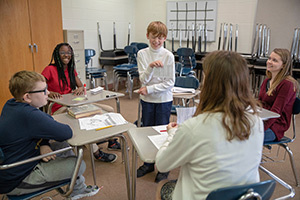 Notre Dame students Natalie Casal (center, back facing camera) and Emma Jones (right) work with students (left-right) Cameron Cook, Braiona Jones and Levi Pieri (standing) during their Latin class at Clay International Academy. Photo by Barbara Johnston/University of Notre Dame.
