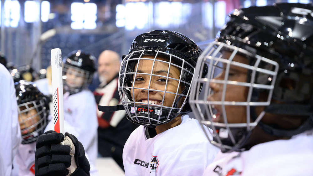 Curtis Lee, 11, smiles on the bench at the Compton Family Ice Arena. Photo by Matt Cashore/University of Notre Dame.