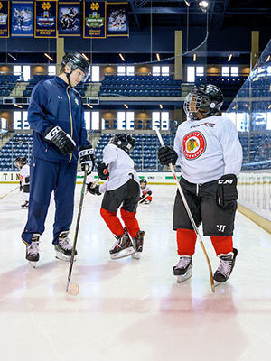 Jon Williams III, right, tries out his new skates on the main ice at Compton Family Ice Arena. Photo by Matt Cashore/University of Notre Dame.