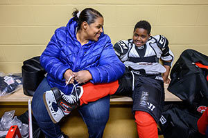 Lateese Williams helps her son Jon, 10, put on his new hockey gear in a Compton Family Ice Center locker room. Photo by Matt Cashore/University of Notre Dame.