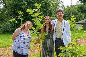 Student interns from the Center for Civic Innovation and Bowman Creek Educational Ecosystem, (names left-right) Annaliza Canda from Purdue University, Isaac Huston from Michigan State University and Tiffany Good from Indiana University SB stand in a native tree nursery that they helped plant and maintain on a former vacant lot in South Bend. Photo by Barbara Johnston/University of Notre Dame.
