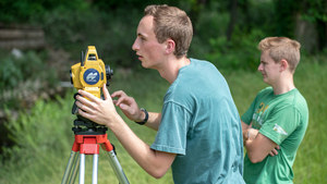 Student interns with the Center for Civic Innovation and Bowman Creek Educational Ecosystem, Finn Cavanaugh and Tommy Crooks (right) from Notre Dame, survey an area of Bowman Creek in South Bend. Photo by Barbara Johnston/University of Notre Dame.
