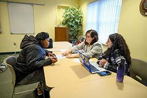 Notre Dame Law School students Stephanie Rahl and Mary Rofaeil (right) provide legal assistance to Christine Smith at the YWCA in South Bend. Photo by Barbara Johnston/University of Notre Dame.