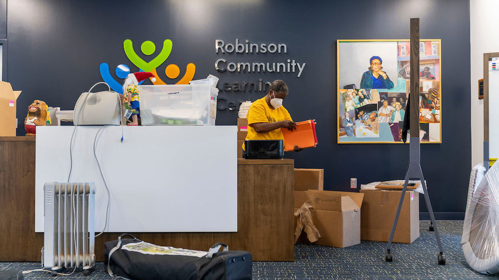 Luella Webster, adult programs coordinator, unpacks boxes behind the reception desk at the new Robinson Community Learning Center (RCLC) in South Bend. Photo by Barbara Johnston/University of Notre Dame.