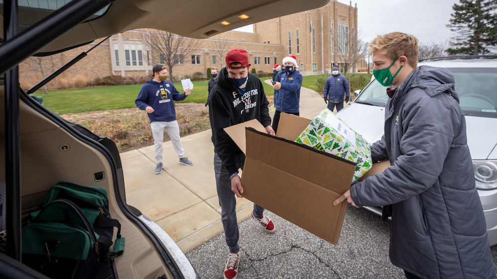 Notre Dame Hockey team members Brady Bjork, left, and Spencer Stastney load gifts into a car outside the Compton Family Ice Arena. (Photo by Matt Cashore/University of Notre Dame)