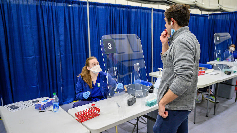 Student EMT Katie Steenvoorden '21, watches as Andrew Seketa '21 gets a sample for testing in the nasal swab testing area of the University's COVID testing facility in the Joyce Center. (Photo by Matt Cashore/University of Notre Dame)