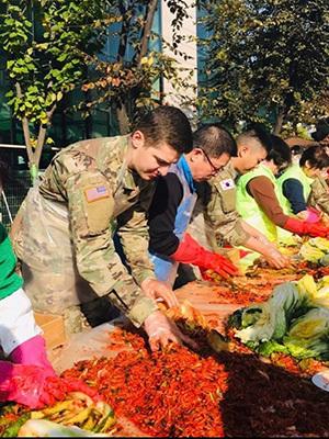 Josh Korhorn performing volunteer work at a local charity food drive while in Korea