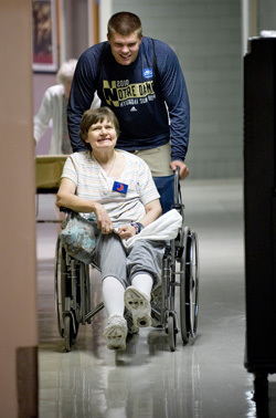Notre Dame Football player Bruce Heggie visits with a resident of Healthwin Specialized Care Facility