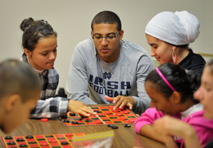 Notre Dame Football player Robert Blanton plays checkers with Michiana refugee children at the Red Cross of St. Joseph County in South Bend