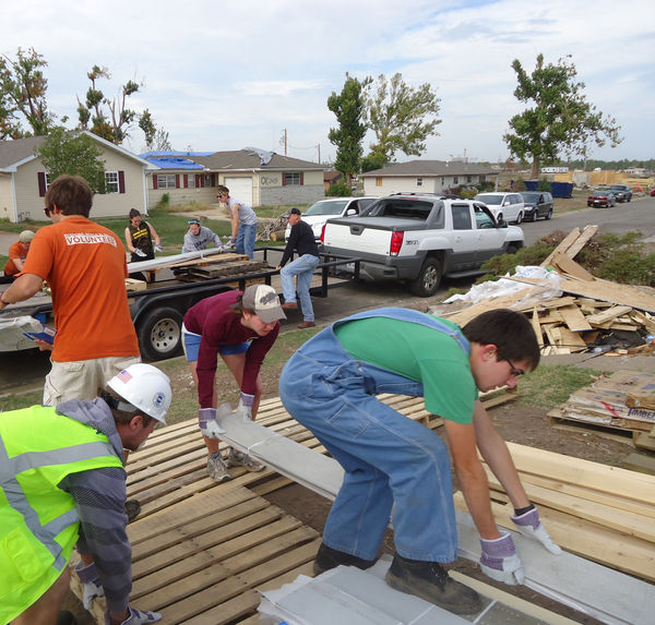 Members of the Notre Dame drumline and trombone section work with other volunteers in a Joplin neighborhood