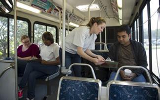 Notre Dame students taking surveys of city bus passengers