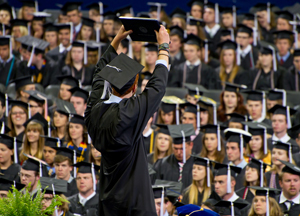 A male student raises his diploma to the crowd