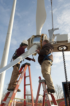 Workers installing wind turbine