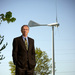 Thomas Corke standing in front of a wind turbine.
