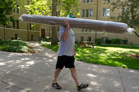 A father carries a rolled carpet across campus