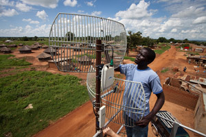 An employee of BOSCO Uganda adjusts an antenna