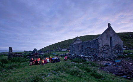 Team members end their day around a campfire made from driftwood in front of the ruins of St. Leo's church, Inishark Island, Ireland.